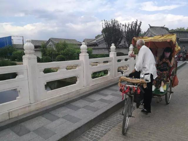 安林在给来自云南的游客讲万宁桥的历史。